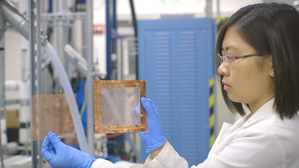 Graduate student Chong Liu holds a newly created nanofilter that efficiently removes tiny pollution particles from the atmosphere. (Photo: Kurt Hickman)